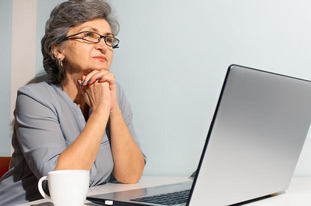 Mulher sênior do retrato usando o laptop. mulher idosa, pensativa, olhando para o lado. conceito de videochamada, novo normal, auto-isolamento