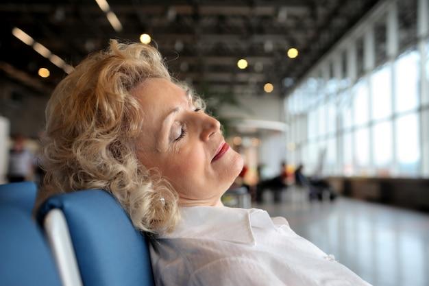 Mulher sênior, dormir, em, a, aeroporto