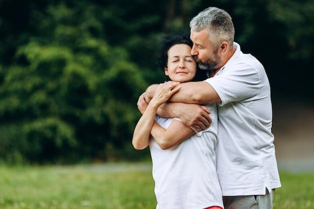 Mulher sênior e homem em pé e abraçando ao ar livre, homem beijando mulher. relações. horizontal