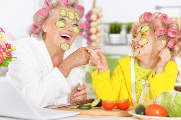Mulher sênior e neta na cozinha com vegetais e laptop