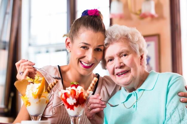 Mulher sênior, e, neta, tendo divertimento, comer, sorvete sundae, em, café