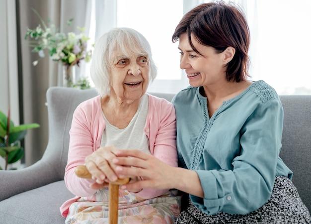 Mulher sênior e sua filha jovem se abraçando em casa. avó com neta momentos familiares juntos