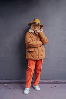 Mulher sênior elegante com roupas quentes. corpo inteiro de mulher idosa confiante em trajes da moda