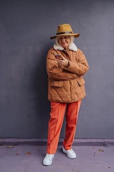 Mulher sênior elegante em roupas quentes com smartphone. corpo inteiro de mulher idosa e confiante