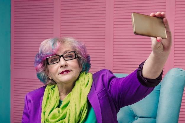 Mulher sênior elegante usando smartphone dourado e fazendo selfie