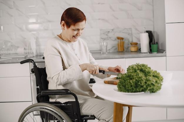 Mulher sênior em cadeira de rodas, cozinhando na cozinha. pessoas com deficiência