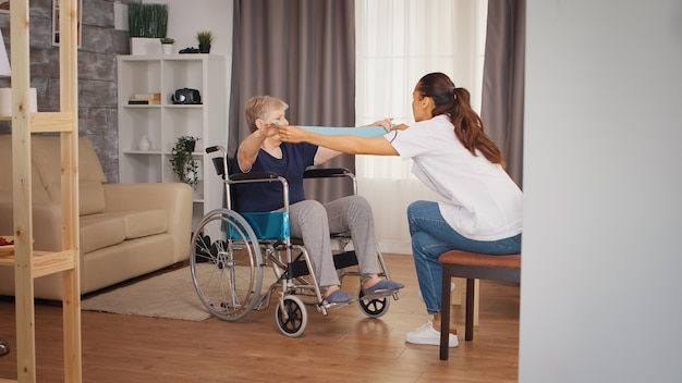 Mulher sênior em cadeira de rodas, fazendo reabilitação com banda de resistência. treinamento, esporte, recuperação e levantamento de peso, lar de terceira idade, enfermagem de saúde, apoio à saúde, assistência social, médico e domiciliar