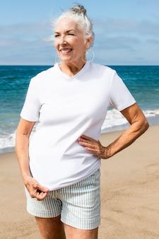 Mulher sênior em camiseta branca na praia