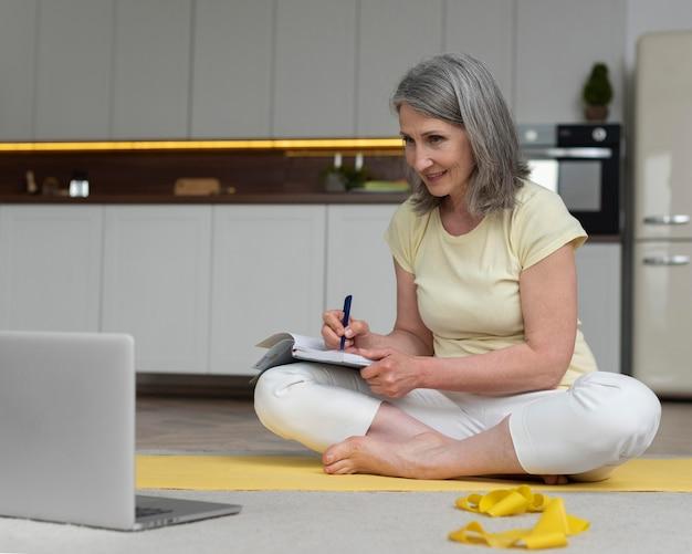 Mulher sênior em casa estudando aula de ginástica no laptop e fazendo anotações