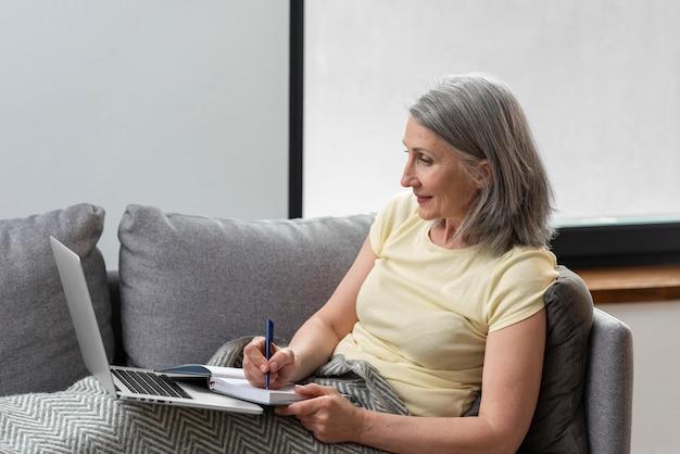 Mulher sênior em casa no sofá usando laptop e fazendo anotações