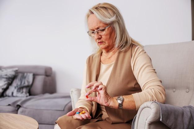 Mulher sênior em casa sentada em sua cadeira e segurando a mão cheia de comprimidos e vitaminas.
