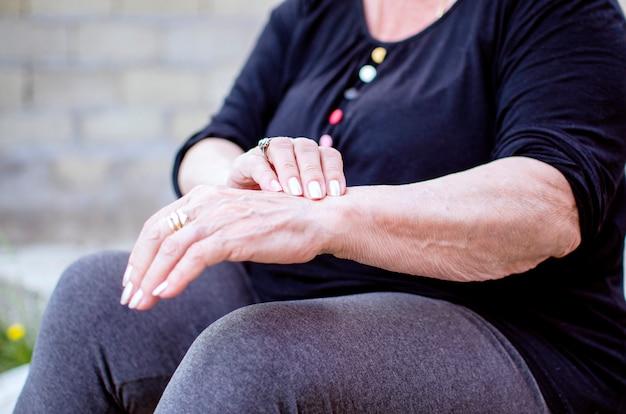Mulher sênior em casa, sofrendo de artrite. mulher sênior, esfregando o pulso e o braço que sofrem de dor de reumatismo na articulação da mão