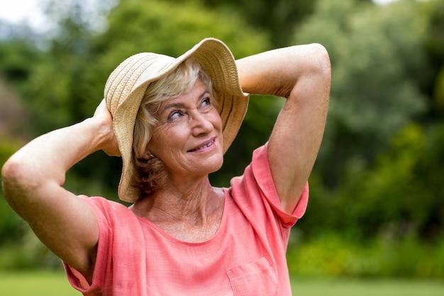 Mulher sênior em pé de chapéu no quintal