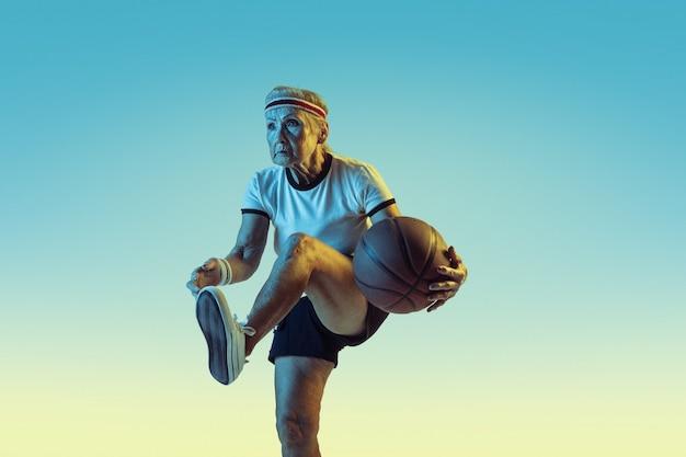 Mulher sênior em roupas esportivas jogando basquete em gradiente
