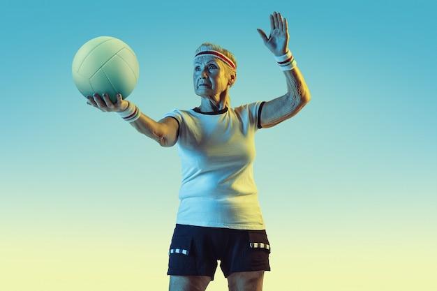 Mulher sênior em roupas esportivas treinando voleibol em parede gradiente