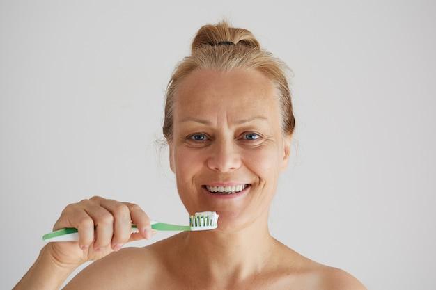 Mulher sênior escovando os dentes com uma escova de dentes como rotina matinal saudável