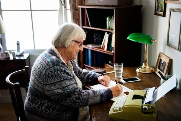 Mulher sênior, escrevendo em um papel