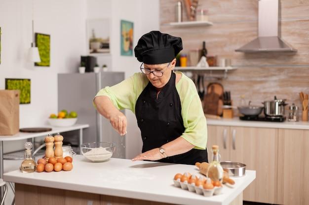Mulher sênior, espalhando farinha na cozinha em casa para produtos de panificação. feliz chef idoso com uniforme polvilhando, peneirando ingredientes crus com a mão, assando pizza caseira.