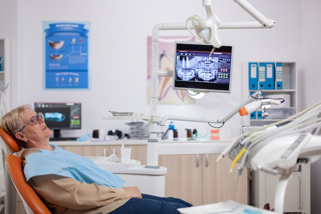 Mulher sênior esperando stomatolog sentado na cadeira laranja para consulta. paciente idoso durante o exame médico com dentista no consultório odontológico com equipamento laranja.