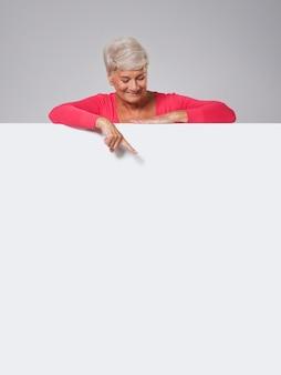 Mulher sênior espiando no quadro branco