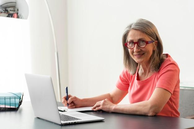 Mulher sênior estudando em casa enquanto usa o laptop e faz anotações Foto Premium