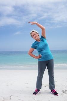 Mulher sênior exercitando na praia
