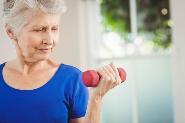 Mulher sênior, exercitar, com, dumbbells, casa