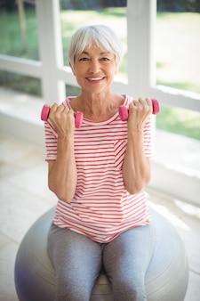 Mulher sênior exercitar com dumbells em casa