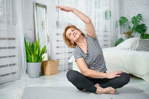 Mulher sênior exercitar enquanto está sentado em posição de lótus