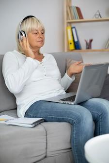 Mulher sênior fazendo uma aula online em seu laptop em casa