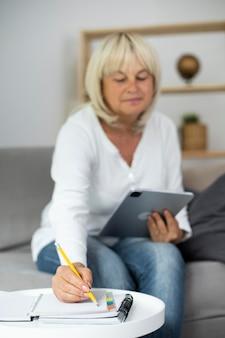 Mulher sênior fazendo uma aula online em seu tablet