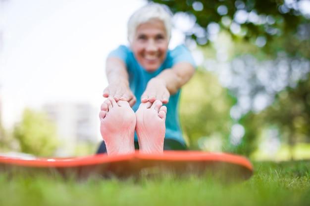 Mulher sênior fazendo yoga e pernas alongamento no parque