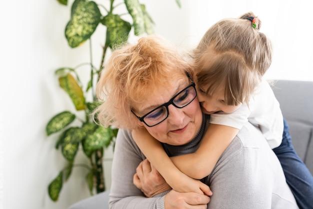 Mulher sênior feliz abraçando seu lindo neto na cozinha em casa.
