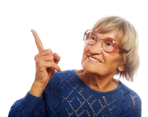 Mulher sênior feliz apontando para cima, isolado no fundo branco