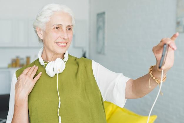 Mulher sênior feliz assistindo vídeo no celular