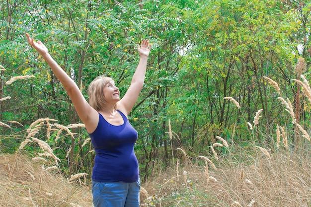 Mulher sênior feliz braços para cima e respirando profundamente ao ar livre com a natureza no fundo do parque.