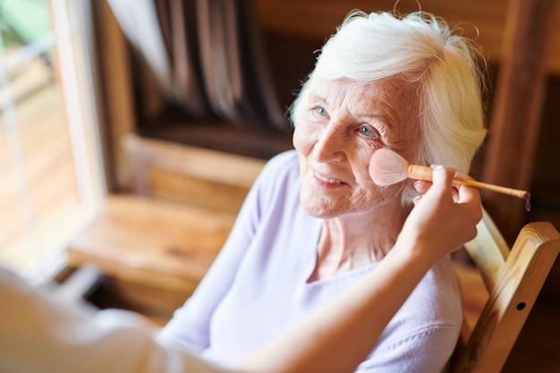 Mulher sênior feliz com cabelo branco curto, olhando para a esteticista durante o procedimento de maquiagem no salão de beleza