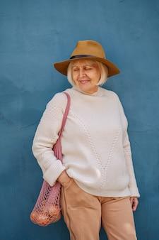 Mulher sênior feliz com saco de pano. idosa alegre carregando um saco de tecido com a mercearia