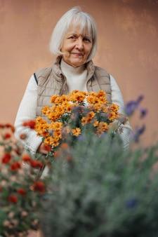 Mulher sênior feliz cuidando das flores. alegre jardineira idosa sorrindo