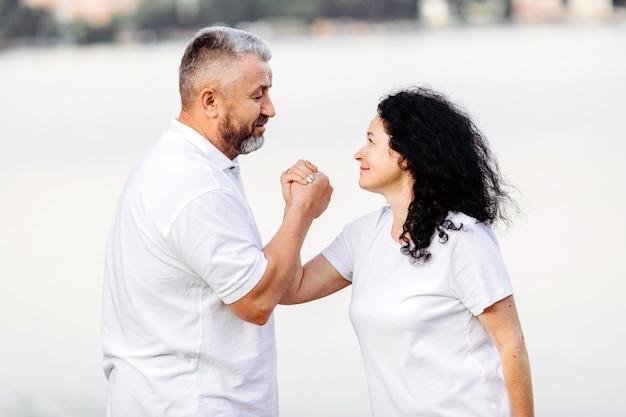 Mulher sênior feliz e homem sênior tomando exercício queda de braço, olhando um ao outro. esporte