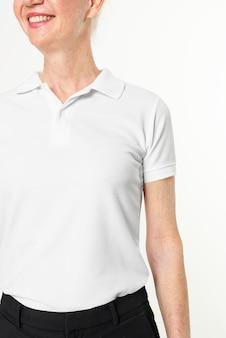 Mulher sênior feliz em camisa pólo branca com retrato de estúdio de design space close-up