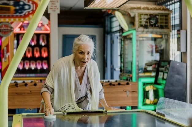 Mulher sênior feliz jogando hóquei de mesa no fliperama