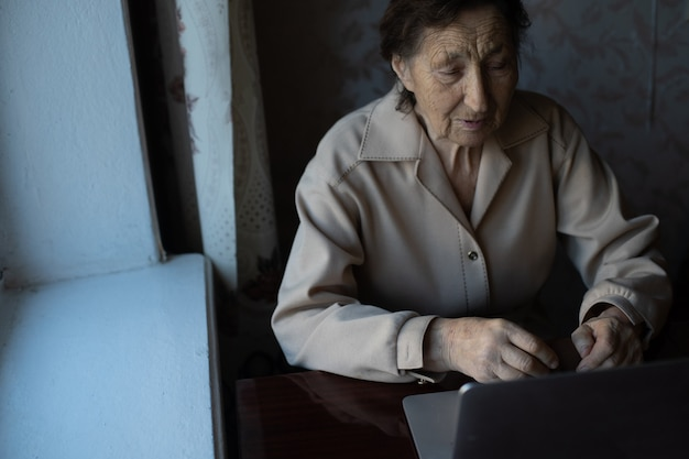 Mulher sênior feliz sentada com a neta, olhando para o laptop, fazendo chamada de vídeo. senhora madura falando com a webcam, fazendo bate-papo online em casa durante o auto-isolamento. tempo para a família durante corona