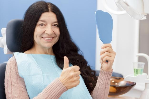 Mulher sênior feliz sorrindo para o espelho na clínica odontológica