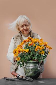 Mulher sênior feliz transplantando flores em vasos no jardim. positivo feminino plantando flores desabrochando