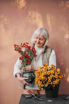 Mulher sênior feliz transplantando flores em vasos no jardim.