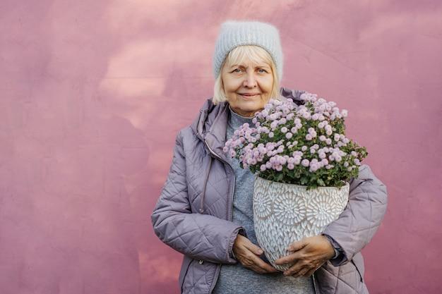 Mulher sênior feliz vestindo casacos, sorrindo para a câmera e carregando flores em vasos