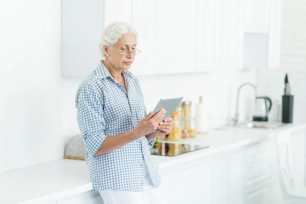 Mulher sênior, ficar, em, cozinha, olhar, tablete digital