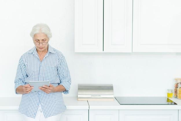 Mulher sênior, ficar, em, cozinha, usando, tablete digital