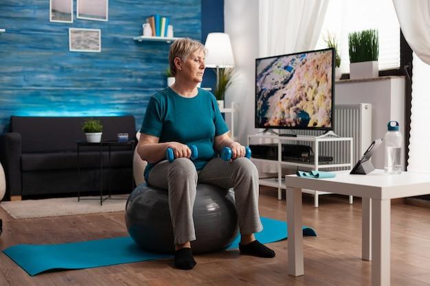 Mulher sênior focada em roupas esportivas assistindo a um treino de fitness online em um tablet, sentada na bola suíça, exercitando os músculos do corpo
